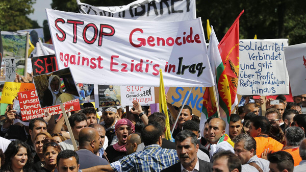 "Kurds of the ethnic minority of Yazidis hold up a banner reading ""Stop genocide against Yazidis in Iraq"" as they march through the streets of Bielefeld August 9, 2014.  Some 10,000 ethnic Kurds of the Yazidis sect, who practice an ancient faith related to Zoroastrianism, protested in the western German city on Saturday against Islamic State (IS) militants, who are surging across northern Iraq near the Kurdistan borders in their drive to eradicate unbelievers such as Christians and Yazidis.    REUTERS/Wolfgang Rattay    (GERMANY - Tags: CIVIL UNREST POLITICS RELIGION)"